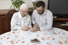 Credit for the older person.The contract of donation. Credit Agreement. The contract of donation. Credit greement. Grandma signs the contract documents Stock Photos