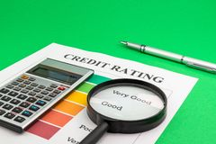 Credit rating with pen, magnifying glass and calculator. Credit rating with pen, calculator and magnifying glass on a green table royalty free stock image