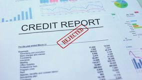 Credit report rejected, hand stamping seal on official document, statistics