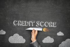 Credit score concept. On black blackboard with businessman hand holding paper plane royalty free stock photos