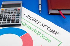 Credit score report with calculator on a blue table. Credit score report with keyboard and notepad on a blue table royalty free stock photo