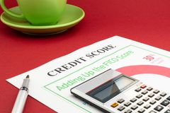 Credit score report with calculator on a red table. Credit score report with keyboard and notepad on a red table royalty free stock photos