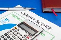 Credit score report with calculator on a blue table. Credit score report with keyboard and notepad on a blue table stock photography
