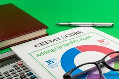 Credit score report with pen and notepad. Credit score report with pen, calculator, glasses and notepad on a green table royalty free stock photo