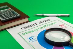 Credit score report with pen and notepad. Credit score report with pen, calculator, magnifying glass and notepad on a green table stock photo