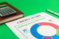 Credit score report with pen and notepad. Credit score report with pen, calculator and notepad on a green table royalty free stock image