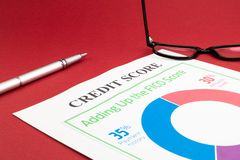 Credit score report with pen and notepad. Credit score report with pen and notepad on a red table royalty free stock photos