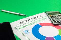 Credit score report with pen and smartphone. Credit score report with pen, calculator and smartphone on a green table stock photos
