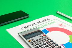 Credit score report with pen and smartphone. Credit score report with pen, calculator and smartphone on a green table stock images