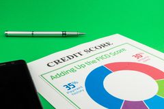 Credit score report with pen and smartphone. Credit score report with pen and smartphone on a green table stock photo
