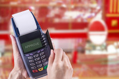 Credit. Women Hands swiping Credit card on Credit card machine or Credit card Terminal on Gold shop background, with Clipping path Stock Photography