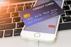 Creditcard gezet naast mobiele telefoon op laptop toetsenbord stock foto's