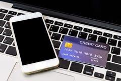 Creditcard gezet naast mobiele telefoon op laptop toetsenbord stock fotografie