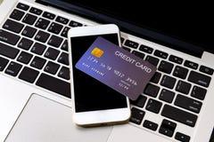 Creditcard gezet op mobiel telefoon en laptop toetsenbord royalty-vrije stock foto's