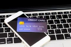 Creditcard gezet op mobiel telefoon en laptop toetsenbord stock afbeeldingen