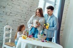 Cree una atmósfera de Pascua junta La familia de amor dice a su hija sobre el conejito de pascua y las tradiciones del día de fie fotos de archivo libres de regalías