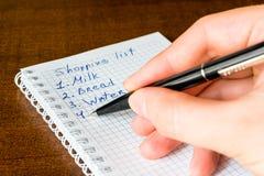 Cree una lista shoping para el paseo a la tienda, escriba las compras foto de archivo libre de regalías
