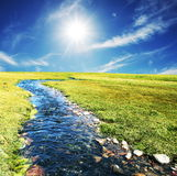 Creek. Blue creek on green grassland Stock Photography