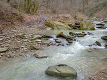 Creek flowing among large stones. Stream flowing among rocks in the forest Stock Photo