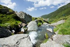 Creek flowing through mountains Royalty Free Stock Images