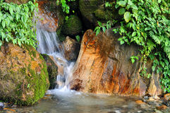 Creek flowing between rocks Royalty Free Stock Image