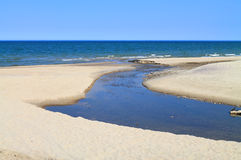 The creek flows into the sea. Freshwater stream flows into the Baltic Sea Royalty Free Stock Photography