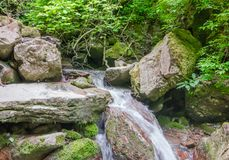 The Creek fluye abajo entre las piedras grandes Foto de archivo libre de regalías