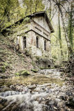 Creek in forest with old house Stock Images