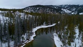 Creek is formed at the edge of an ice covered lake in winter. Little Redfish lake feeds a creek with water in winter stock video
