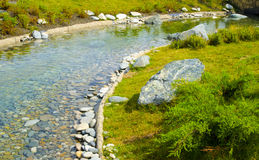 A Creek in the Park. The bottom of a stream lined with stones Royalty Free Stock Photos