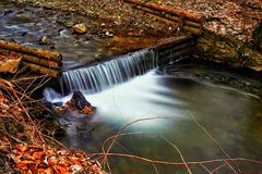 Creek riffle. A creek riffle over a small wooden dam Stock Image