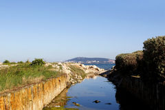 Creek. A small Creek of discharges into the sea and in the background is the town of Sete in France royalty free stock photography