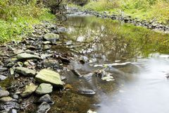 Creek with stones and reflection. Beautiful creek in forest during fall Royalty Free Stock Image