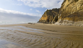 Creek Waters Along the Beach. A small creek reaches the Pacific Ocean along an Oregon beach Royalty Free Stock Images
