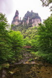Creekside with bridge in yangjiajie. Creekside view with a small bridge. Yangjiajie scenic area in china. Tall obelisk stone with deep valleys stock images