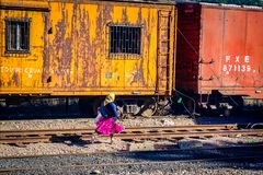 Tarahumara woman running for the train in Creel, Mexico. CREEL, MEXICO-Jan 2016: A native Raramuri woman in bright clothing runs across railway tracks while Stock Image