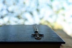 Creencia b?blica de la fe de la escritura de plata de la cadena de la cruz del libro de la biblia fotos de archivo libres de regalías