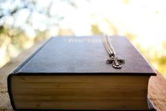 Creencia b?blica de la fe de la escritura de plata de la cadena de la cruz del libro de la biblia imagenes de archivo