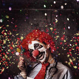 Creepy birthday clown at party celebration. Insane circus clown with smile holding miniature balloons under falling confetti during a birthday party celebration Stock Photos
