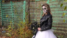 Creepy bride with a bouquet of black flowers and make-up in the form of a skull. A creepy bride with a bouquet of black flowers and make-up in the form of a stock footage