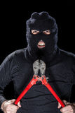 Creepy Burglar. A burglar wearing a balaclava holding huge wire cutters over black background royalty free stock image