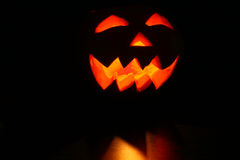 Creepy carved pumpkin face in dark Royalty Free Stock Photos