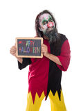 Creepy Clown holding a sign, colorful Text Happy Halloween, isol Royalty Free Stock Photo