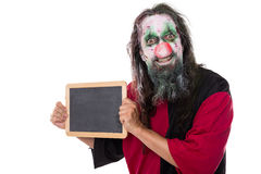 Creepy Clown holding a sign with copyspace, isolated on white. Creepy Clown holding a sign, copyspace, isolated on white, concept Halloween and make up stock image