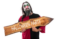 Creepy clown holding a wooden arrow with Text Halloween Party, i. Creepy clown holding a wooden sign with Text Halloween Party, isolated on white stock images
