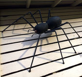 Creepy Crawler. Black spider constructed from metal crawling under the eves stock photo