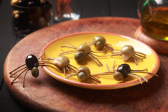 Creepy crawly edible Halloween spiders. Made from cured green and black olives with Italian spaghetti legs on a side table at a Halloween party for appetizers stock photo