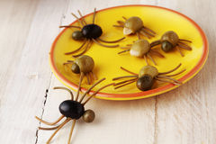 Creepy crawly Halloween spider snacks. For a party celebration made from black and green olives with Italian spaghetti legs served on a yellow plate on a rustic royalty free stock photo