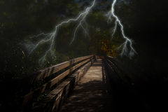 Creepy dark night in the woods on Halloween. Bolts of bright scary lightning burst over a long dark wooden bridge in the forest Stock Image