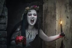 Creepy dead bride with candle screaming. Halloween scene